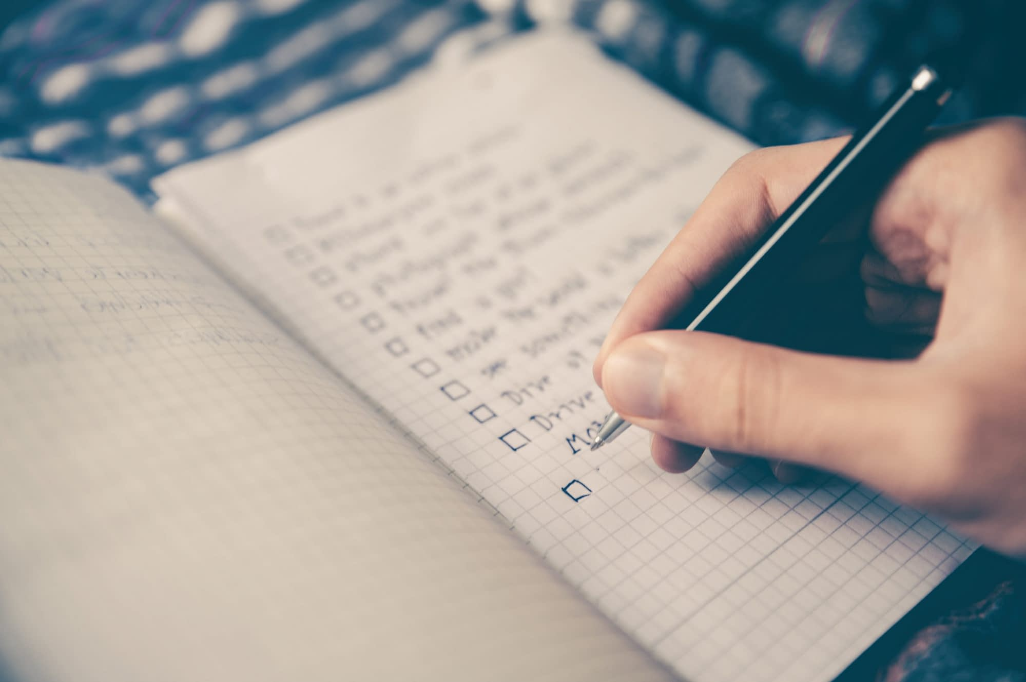 website maintenance services cover with person writing bucket list on book