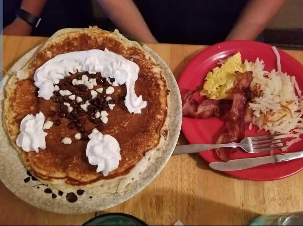 Granny Ds Huge Chocolate Chip Pancakes with a side of eggs, hash browns, and bacon