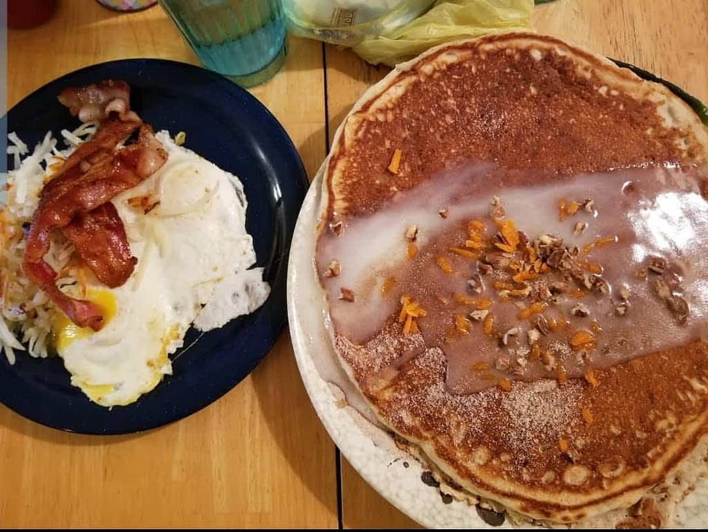 Granny Ds Huge Carrot Cake Pancakes with a side of eggs, hash browns, and bacon