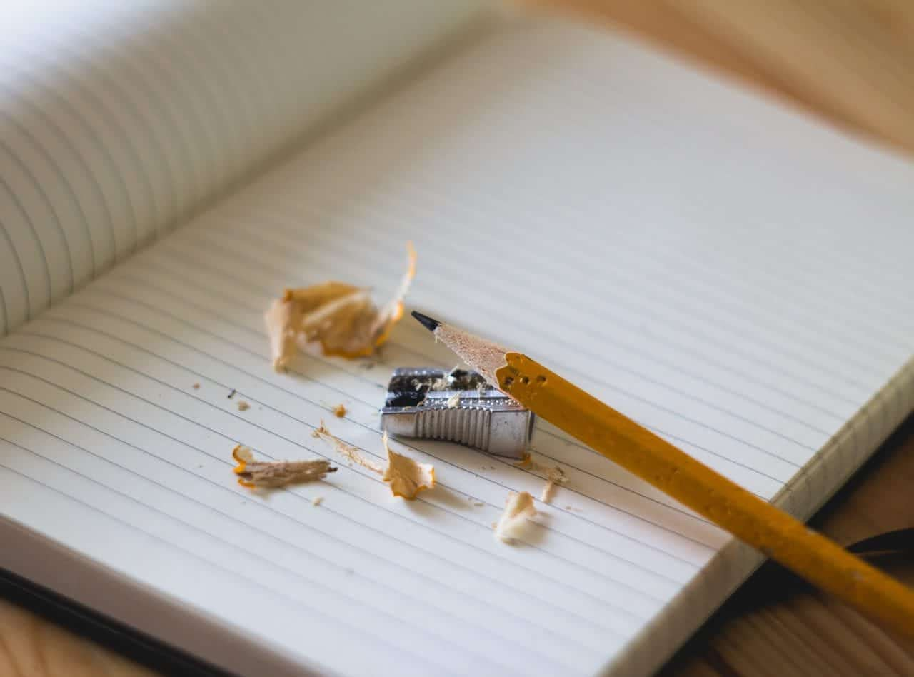 Open notebook with a pencil and sharpener with shavings on a desk top