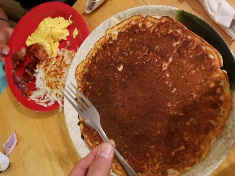 Granny Ds Huge Pancakes with a side of eggs, hash browns, and bacon
